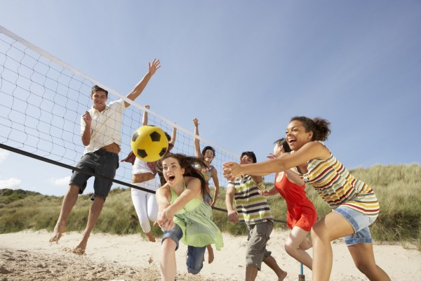 Teenagers playing volleyball on the beach