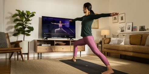 Woman following workout video in living room
